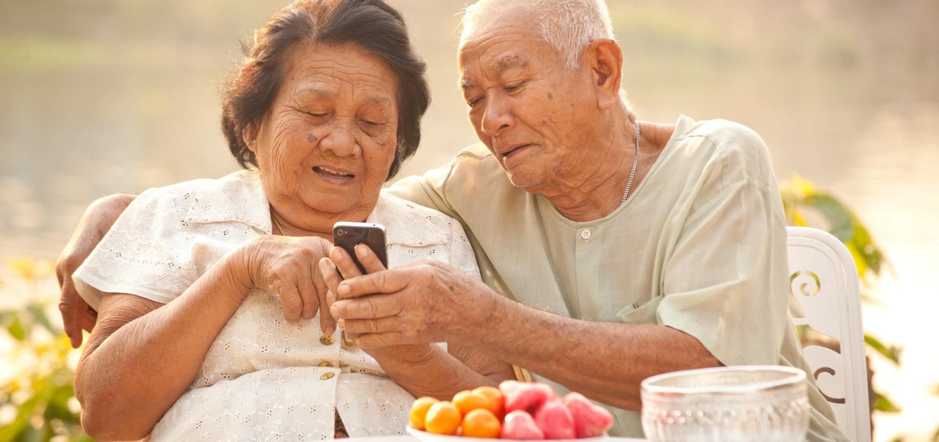 elder couple using mobile phone